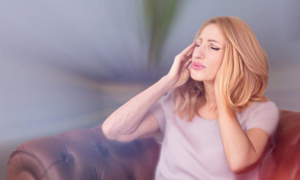 Женщина на диване с головной болью