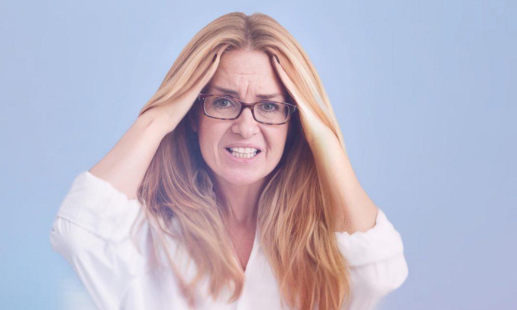 Женщина средних лет испытывает головную боль при мигрени
