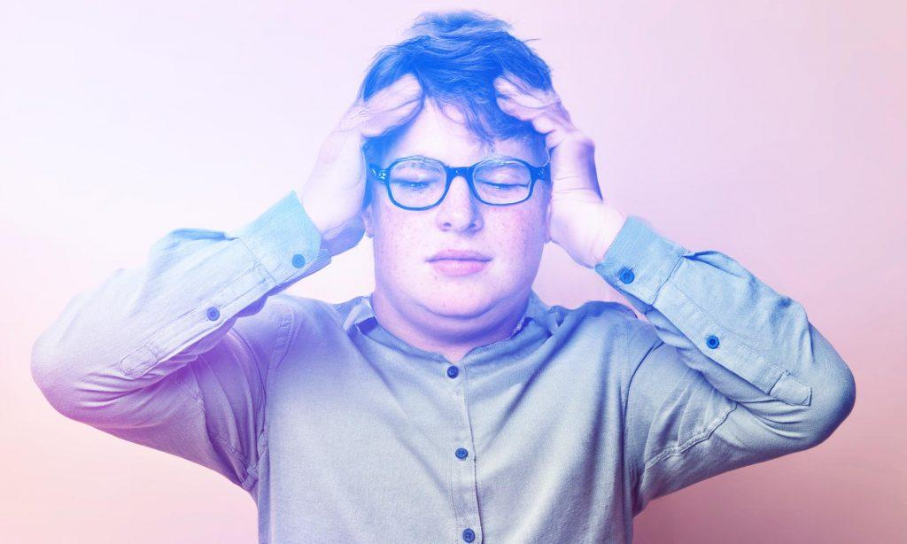 Упитанный молодой человек во время приступа мигрени