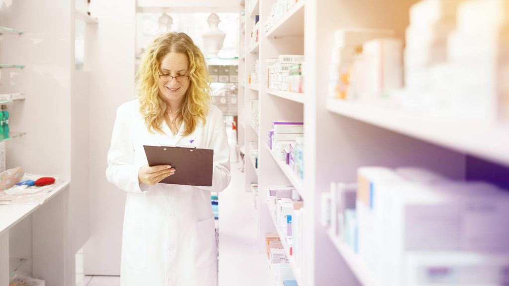 Фармацевт-женщина в аптеке ищет лекарство от головной боли