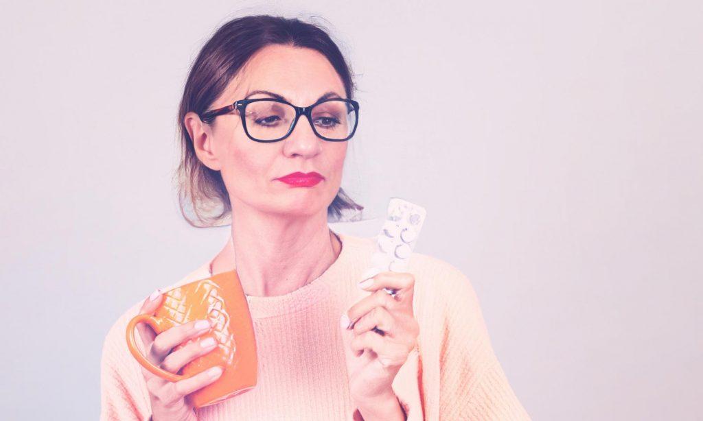 Женщина собирается принять таблетки от мигрени